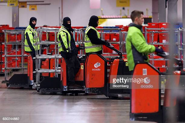 Employees prepare to pull trolley loads of completed customer order crates at the Ocado Group Plc distribution centre in Dordon UK on Friday Dec 16...