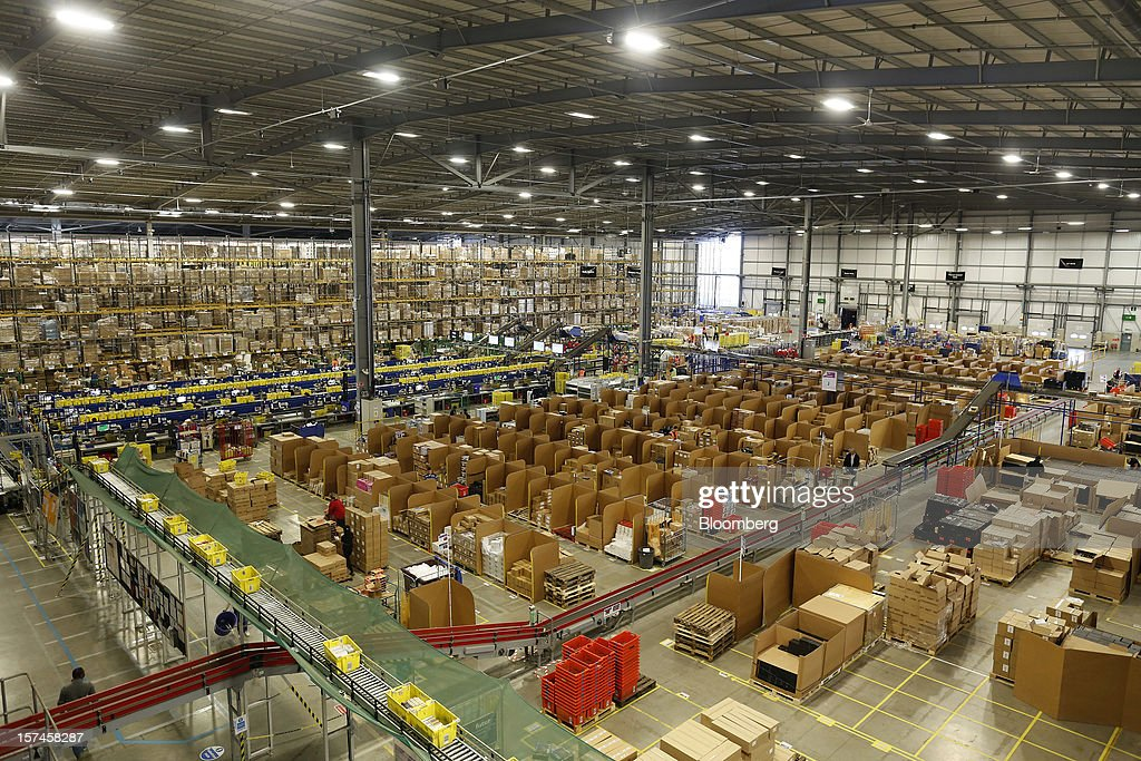 Employees process customer orders at the Amazon.co.uk Marston Gate 'Fulfillment Center,' the U.K. site of Amazon.com Inc. in Ridgmont, U.K., on Monday, Dec. 3, 2012. U.K. consumer confidence unexpectedly increased to an 18-month high in November as Britons become more optimistic about the economy and their finances, GfK NOP Ltd. said. Photographer: Simon Dawson/Bloomberg via Getty Images