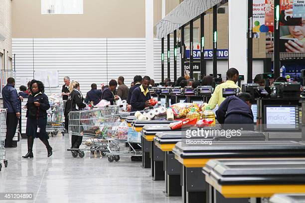 Employees process customers' products at the checkout desks of a Makro cash and carry store operated by Massmart Holdings Ltd in Alberton South...