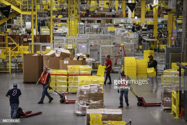 Employees pull pallet trucks at the Amazoncom Inc fulfillment center in Robbinsville New Jersey US on Monday Nov 27 2017 The holiday shopping season...