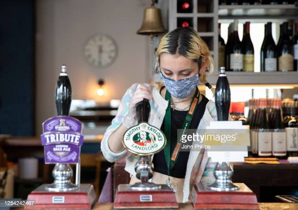 Employees pull pints at the Lordship pub in East Dulwich on July 04, 2020 in London, England. The UK Government announced that Pubs, Hotels and...