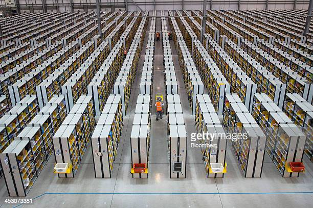 Employees push carts along aisles as they process customer orders ahead of shipping at one of Amazon.com Inc.'s fulfillment centers in Rugeley, U.K.,...