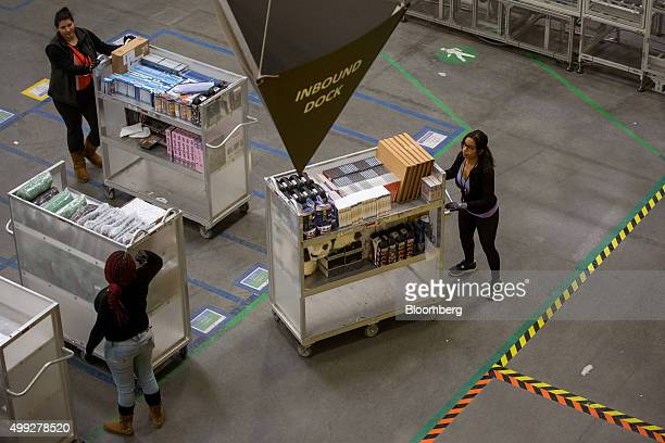 Employees push carts filled with merchandise inside an Amazoncom Inc fulfillment center on Cyber Monday in Robbinsville New Jersey US on Monday Nov...