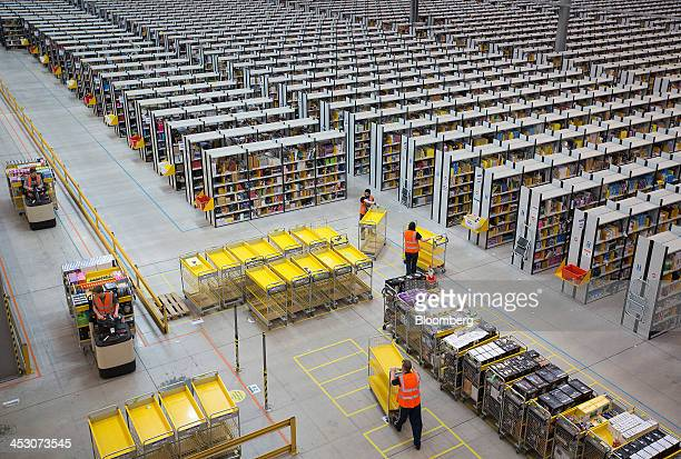 Employees push empty carts as they prepare to process customer orders ahead of shipping at one of Amazon.com Inc.'s fulfillment centers in Rugeley,...