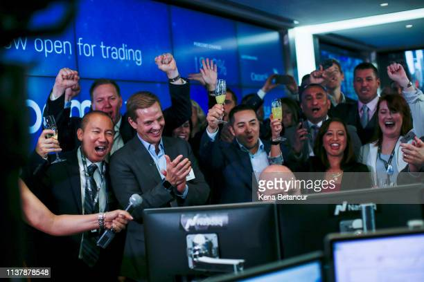 Employees reacts as Jay Heller, head of capital markets & initial public offering execution of Nasdaq Inc, center, opens trading on Zoom Video...