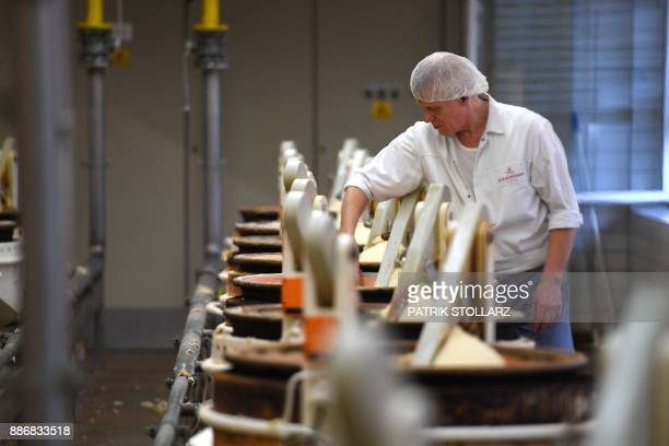 Employees remove freshly cooked marzipan from roasting pots at the headquarters of the traditional confectionary maker JG Niederegger GmbH in Luebeck...