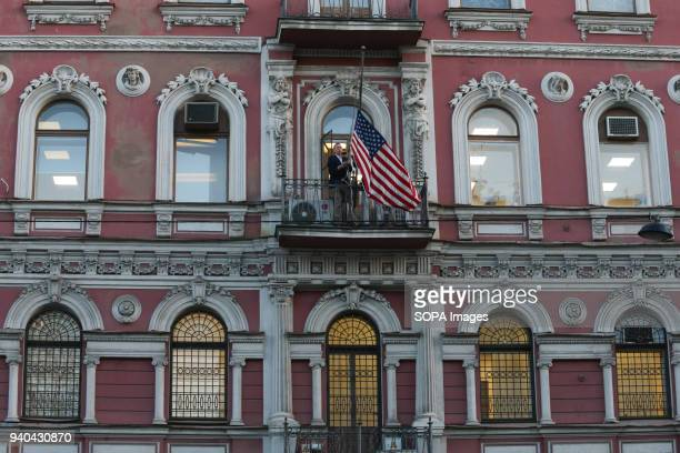 Employees remove the national flag of the United States from the building of the US Consulate General at Furstatskaya Street in St Petersburg Russia...