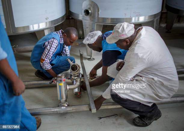 Employees repair a technical plant at beverage manufacturer Kevian Kenya Ltd on May 18 2017 in Thika Kenya