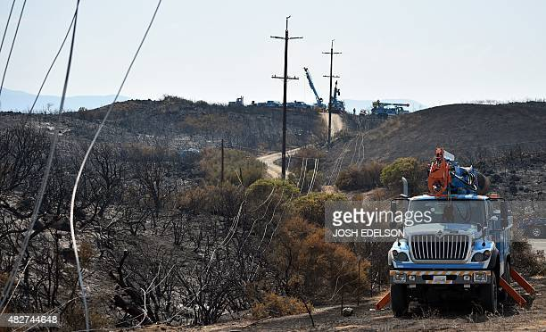 PGE employees repair burned power lines after the Rocky fire went through near Clear Lake California on August 1 2015 The fire has charred more than...