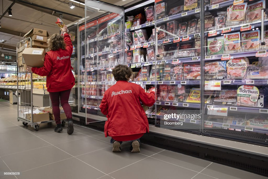 Employees restock a chilled processed meat cabinet inside an