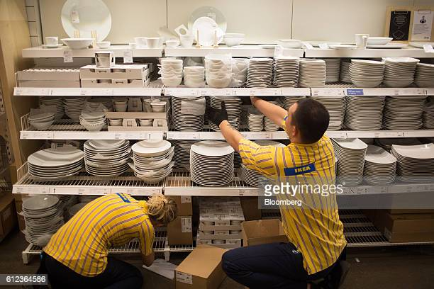 Employees restock a display of white crockery in the Ikea AB retail store in Khimki Russia on Monday Oct 3 2016 Ikea's Russia unit may spend 100...