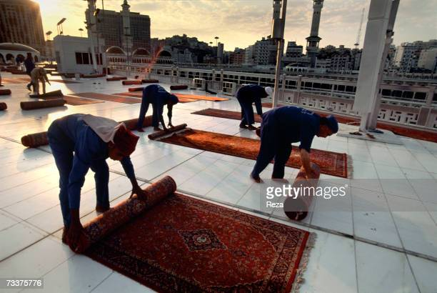 Employees rollup and move prayer rugs after the Asr prayer within the Masjid AlHaram mosque location of the Kaaba Islam's most sacred sanctuary and...