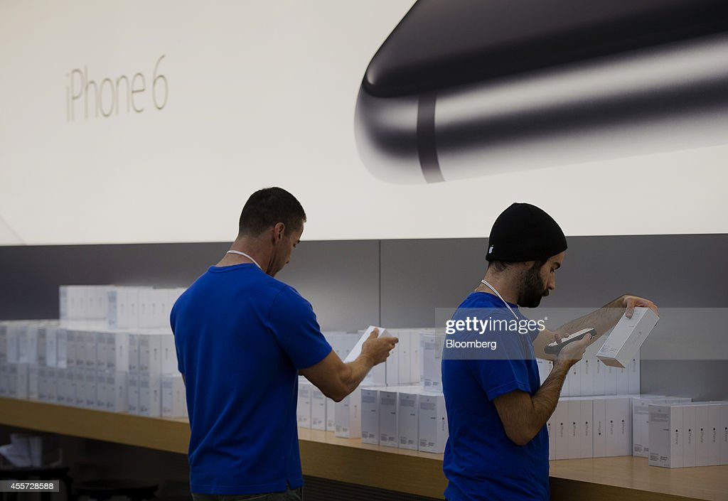 Employees scan iPhone 6 box during the sales launch at the Apple Inc. store in Palo Alto, California, U.S., on Friday, Sept. 19, 2014. Apple Inc.'s stores attracted long lines of shoppers for the debut of the latest iPhones, indicating healthy demand for the bigger-screen smartphones. The larger iPhone 6 Plus is already selling out at some stores across the U.S. Photographer: David Paul Morris/Bloomberg via Getty Images