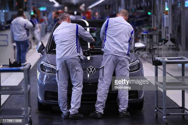 Employees secure a plastic hood fitting to a Volkswagen AG ID.3 electric automobile on the assembly line at the automaker's factory in Zwickau,...