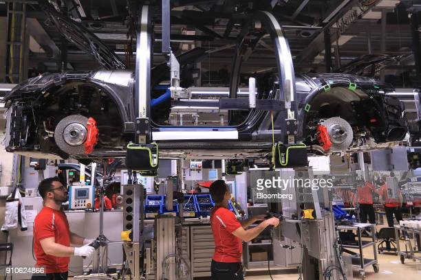 Employees secure a Porsche 911 chassis inside the Porsche AG luxury automobile factory in Stuttgart Germany on Friday Jan 26 2018 Porsche AG will...