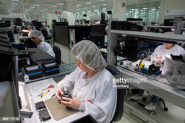 Employees secure leather skins to the bodies of Leica M10 rangefinder digital cameras at the Leica Camera AG factory in Wetzlar Germany on Tuesday...