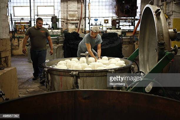 Employees secure packages of raw wool in a tank used to dye wool at the Woolrich Inc woolen mill in Woolrich Pennsylvania US on Wednesday Nov 4 2015...