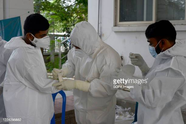 Employees seen wearing personal protective equipment suits before they start their work for the Covid-19 testing. Mugda Medical College and Hospital...