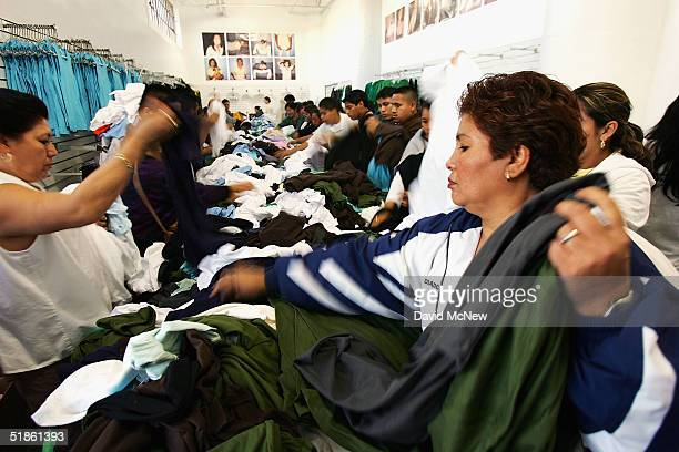 Employees select garments for themselves as they receive a holiday bonus of 80 pieces of clothing to take home at the American Apparel garment...