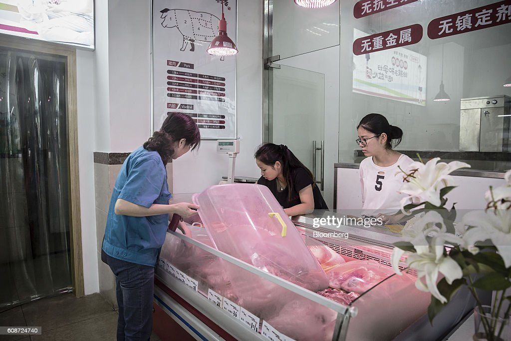 Employees serve a customer shopping for pork at a retail store operated by the Jia Hua antibiotic-free pig farm in Tongxiang, China, on Thursday, Sept. 15, 2016. Hog farmer Shen Jian-Ping has spent 4.7 million yuan ($700,000) giving his swine roomier, better-ventilated digs and there are three full-time veterinarians to help keep the 465-sow herd healthy. Photographer: Qilai Shen/Bloomberg via Getty Images