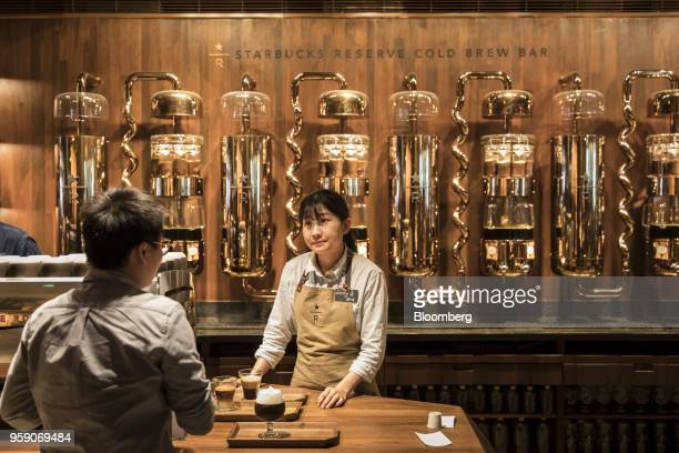 Employees serve beverages on trays at the cold brew bar inside the Starbucks Corp Reserve Roastery store in Shanghai China on Friday May 11 2018...