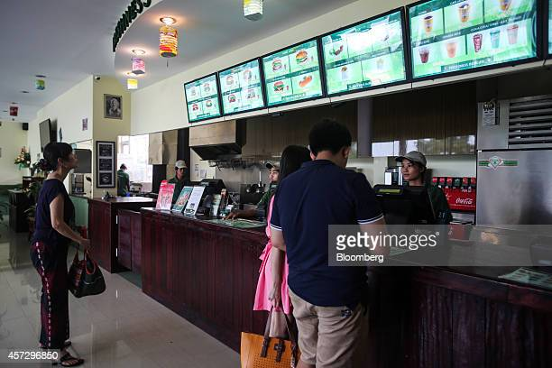 Employees serve customers at a Freshness Burger restaurant operated by 3E Food and Beverage Myanmar Ltd in the Myanmar Culture Valley shopping plaza...
