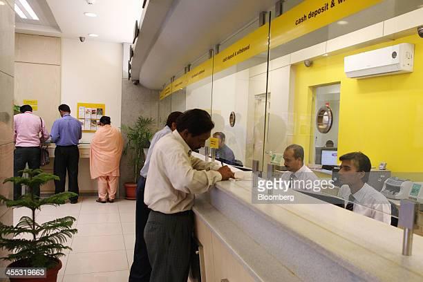 Employees serve customers inside a branch of Soneri Bank Ltd in Karachi Pakistan on Wednesday Dec 11 2013 Soneri a Pakistani lender whose market...
