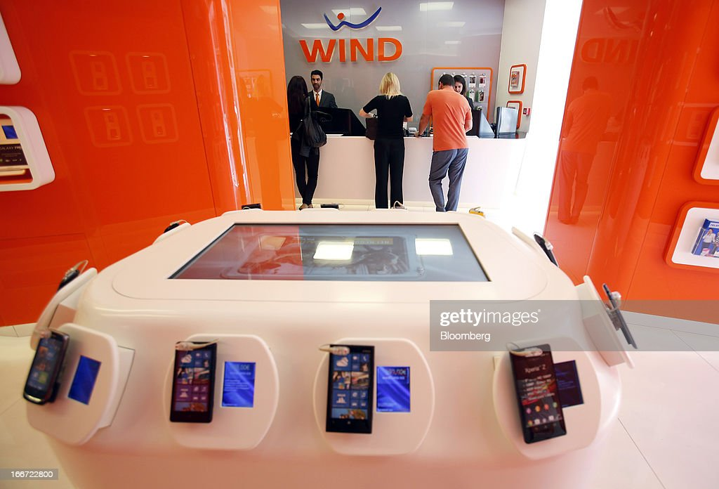 Employees serves customers at a service counter inside a Wind SpA mobile phone store, owned by VimpelCom Ltd., in Rome, Italy, on Monday, April 15, 2013. Italy's state-owned postal service and Wind SpA, the country's third-largest mobile-phone company, are discussing a possible venture with Wind's fixed-line network Infostrada, Poste Italiane SpA Chief Executive Officer Massimo Sarmi said. Photographer: Alessia Pierdomenico/Bloomberg via Getty Images