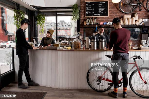 Employees serving customers in cafe, Nike and Coffee shop, New York, USA