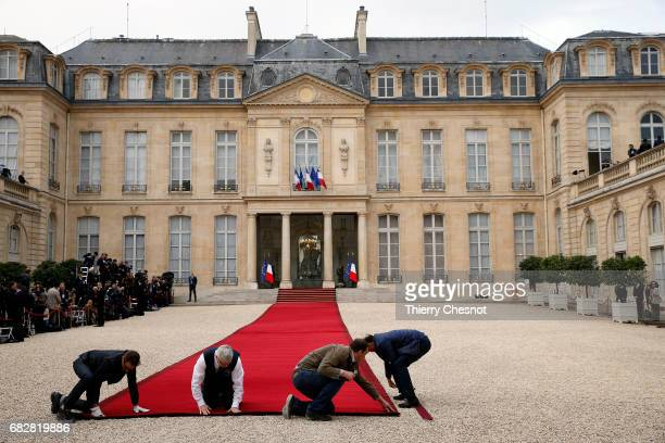 Employees set up the red carpet on the steps of the Elysee Presidential Palace in final preparations for the handover ceremony between France's...