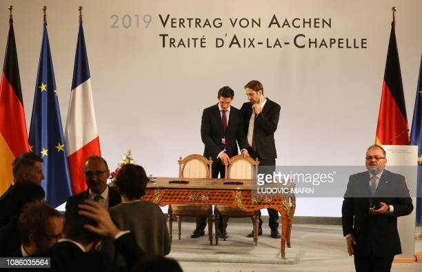 Employees set up the table where the German Chancellor and the French President are to sign a FrenchGerman friendship treaty on January 22 2019 in...