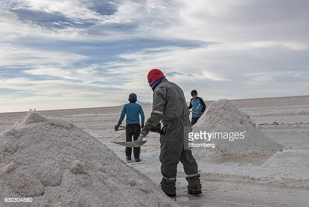 Employees shovel salt into mountains at the Salar de Uyuni in Potosi Bolivia on Sunday Dec 11 2016 Bolivia has the largest lithium deposits of any...
