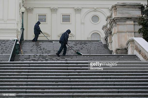 Employees shovel the steps outside the US Capitol in Washington DC US on Monday March 25 2013 An early spring snowstorm tied up air traffic along the...