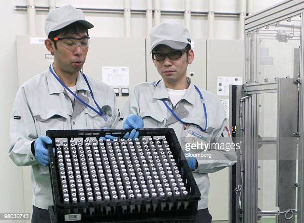 Employees show Panasonic Corp lithiumion batteries on the production line of the company's plant in Suminoe Osaka City Japan on Thursday March 25...