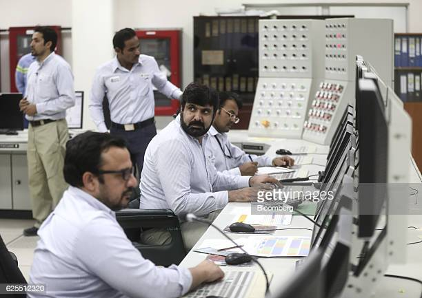 Employees sit and monitor computer screens inside the control room of the phosphate processing plant at the Ras Al Khair Industrial City operated by...