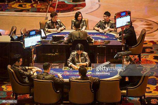 Employees sit at gaming tables at Studio City casino resort developed by Melco Crown Entertainment Ltd ahead of the grand opening during a media tour...