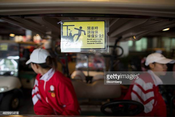 Employees sit in a golf cart at Mission Hills Dongguan operated by Mission Hills Group Ltd in Dongguan Guangdong province China on Friday Dec 21 2013...