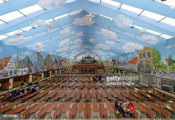 Employee's sit in an empty beer tent as preparations are under way for the Oktoberfest beer festival at the Theresienwiese fair grounds in Munich...