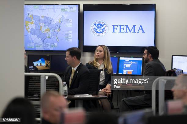 Employees sit in front of computer monitors at the command center of the Federal Emergency Management Agency headquarters shortly before a visit by...