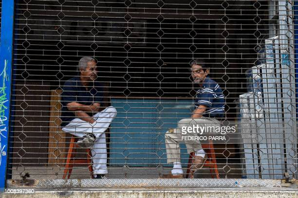 Employees sit inside a hardware store during a partial power cut in Caracas on July 31 2018 A power failure cut electricity to 80 percent of the...