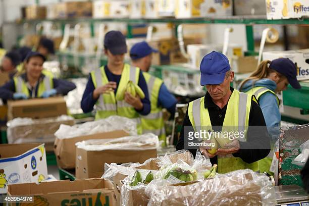 Employees sort bunches of ripe and unripe Fyffes bananas at Fyffes Plc's ripening and fruit distribution plant in Coventry, U.K., on Thursday, Aug....
