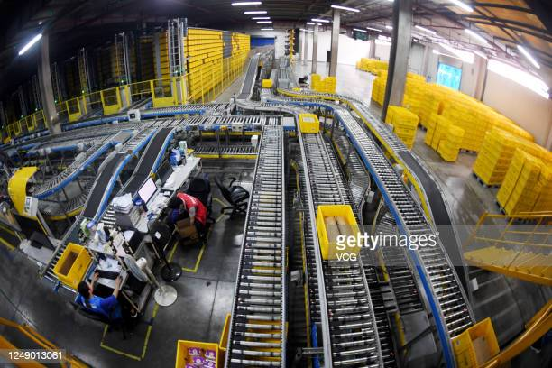 Employees sort out parcels at a logistic base of e-commerce giant Suning before the upcoming 618 Shopping Festival on June 11, 2020 in Nanjing,...
