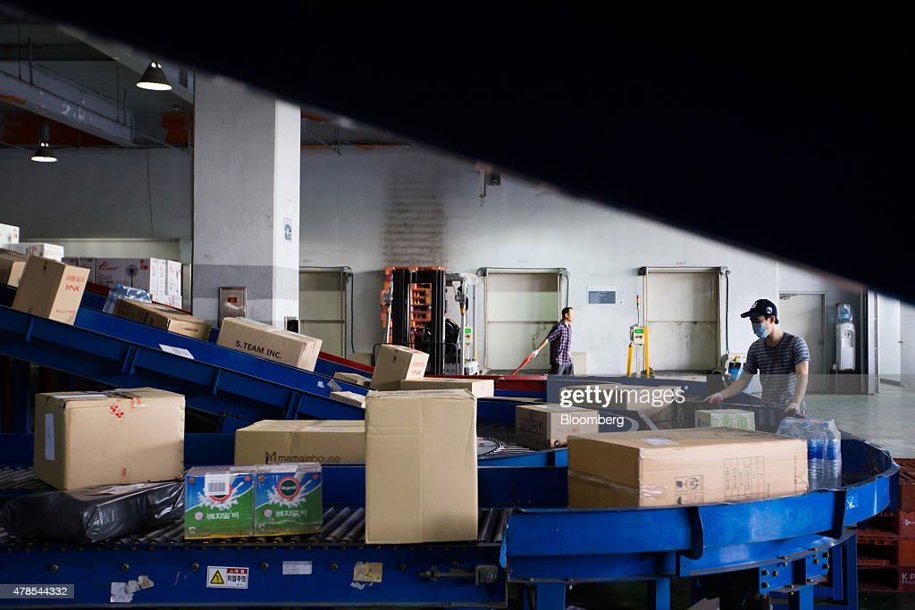 Employees sort parcels as they move along a conveyor at a CJ