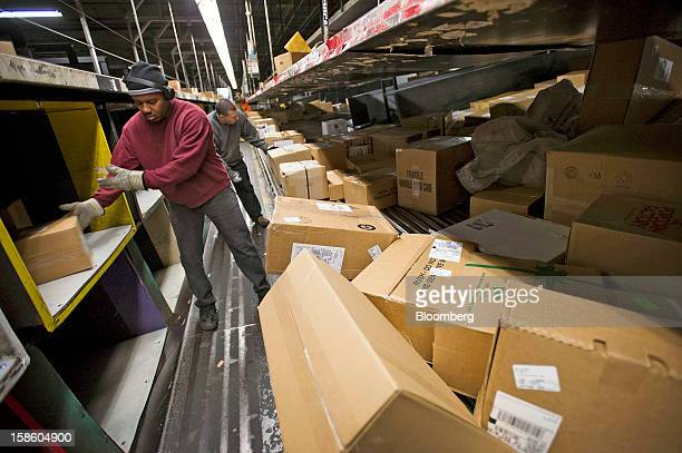 Employees sort through packages at a United Parcel Service Inc sorting facility in San Francisco California US on Thursday Dec 20 2012 UPS the...