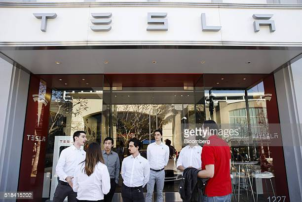 Employees speak with customers waiting in line ahead of the Model 3 announcement outside the Tesla Motors Inc store on the Third Street Promenade in...