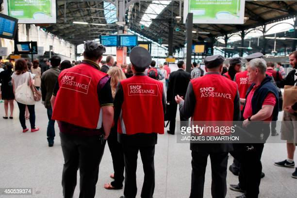SNCF employees speak with travelers at the SaintLazare railway station on June 13 2014 in Paris on the third day of a national strike by French SNCF...