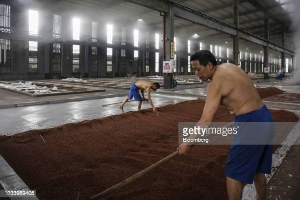Employees spread out steamed sorghum to cool ahead of fermentation at Chongqing Jiangxiaobai Liquor Co.'s Jiangji Distillery in Chongqing, China, on...