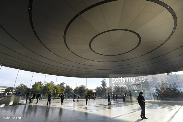 Employees stand among attendees ahead of an Apple Inc event at the Steve Jobs Theater in Cupertino California US on Wednesday Sept 12 2018 Apple will...