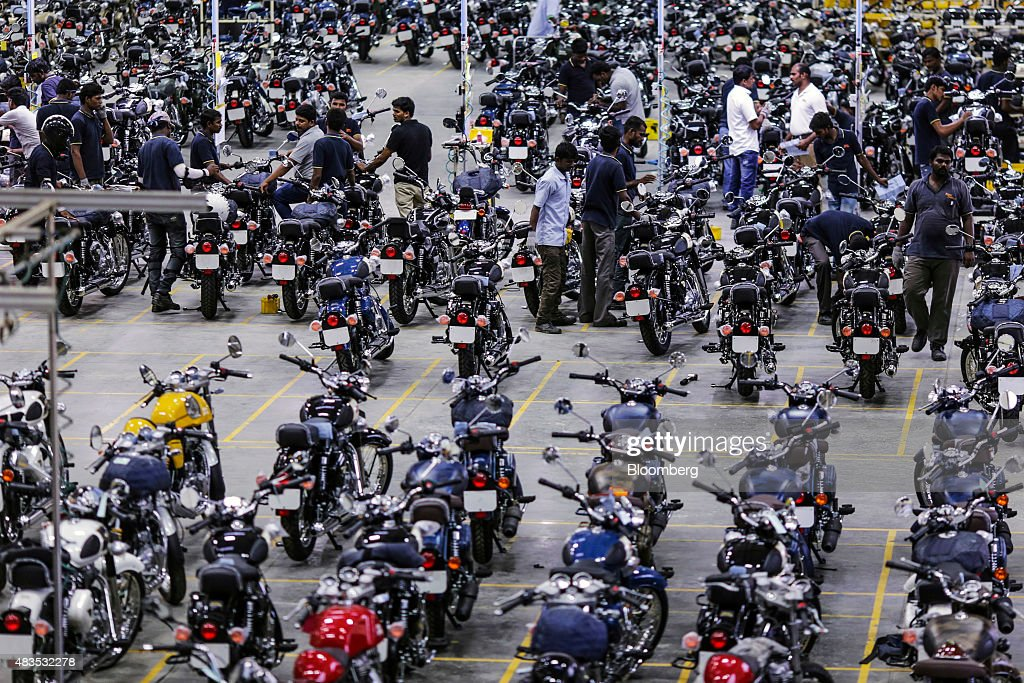 Employees stand among Royal Enfield Motors Ltd motorcycles on the production line at the company`s manufacturing facility in Chennai India on Tuesday.