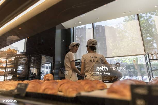 Employees stand behind trays of pastries in the Princi bakery inside the Starbucks Corp Reserve Roastery store in Shanghai China on Friday May 11...